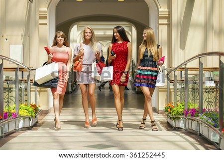 Portrait of a beautiful young four women walking in shop - stock photo