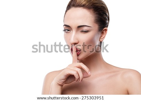 Portrait of a beautiful young girl , Europeans , on a white background with clean skin without make-up , pressing his index finger to the cubes . mystery secret. gesture - stock photo