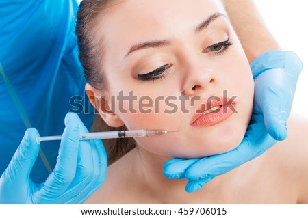 Portrait of a beautiful young girl getting botulinum toxin cosmetic injections, isolated on white background.