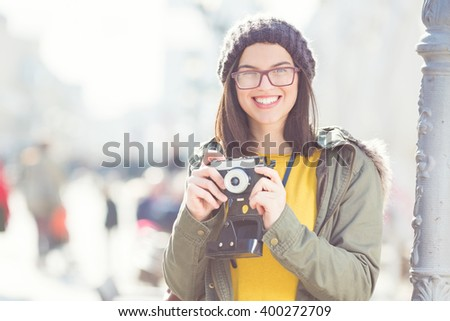 Portrait of a beautiful young girl holding an old-fashion camera and smiling - stock photo