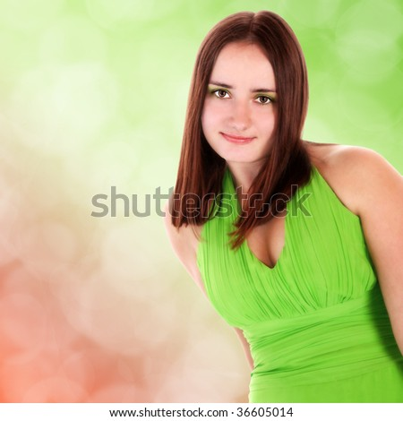 Portrait of a beautiful young girl in party dress on green bokeh background