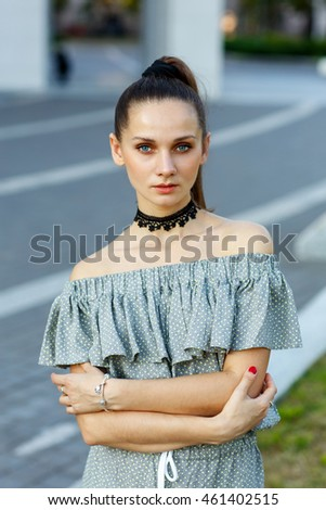 Portrait of a beautiful young girl in stylish dress with choker