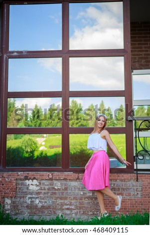 Portrait of a beautiful young girl on the background of the Windows in the Park skirt