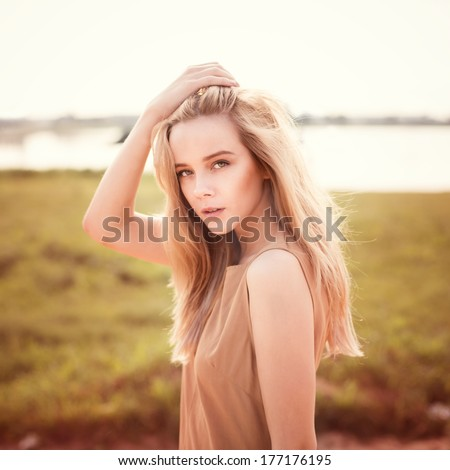 portrait of a beautiful young girl on the beach - stock photo