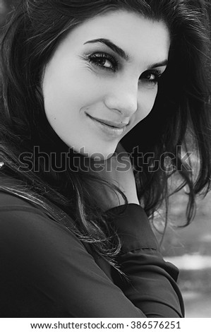 Portrait of a beautiful young girl outdoors. Outdoors portrait of beautiful young brunette woman looking at camera. Closeup sensual portrait of beautiful girl outdoors. Art photo