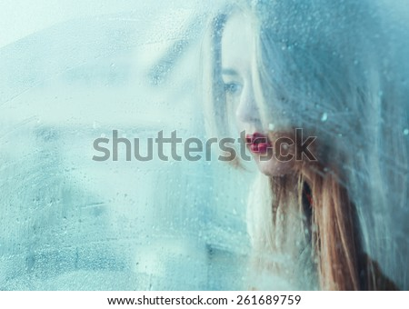 portrait of a beautiful young girl standing at the window watching the rain - stock photo