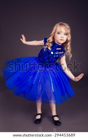 Portrait of a beautiful young girl wearing a fancy blue party gown dress, in studio