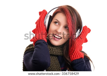 Portrait of a beautiful young girl wearing winter clothes listening to music