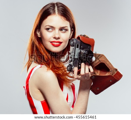 portrait of a beautiful young girl with a camera in the studio