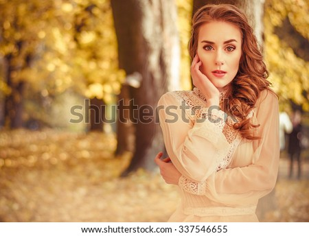 portrait of a beautiful young girl with blond hair in a black chiffon dress against the backdrop of autumn trees - stock photo