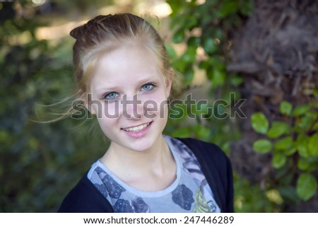 Portrait of a beautiful young girl with blonde hair on nature