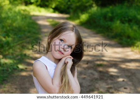 portrait of a beautiful young girl with long hair outdoors in summer