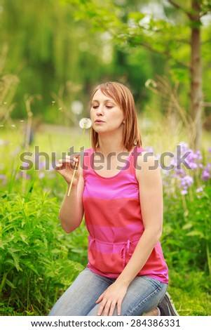 Portrait of a beautiful young girl woman sitting in the forest field meadow with dandelion flower in her hands and blowing it on a bright summer day, funny romantic card with copy space for text - stock photo