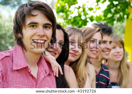 Portrait of a beautiful young guy and friends group - stock photo