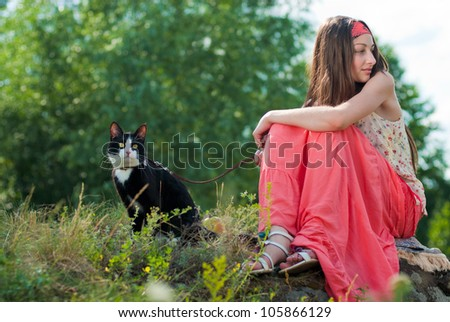 Portrait of a beautiful Young happy smiling teenage girl sitting outdoors on stone rock with black cat on lead - stock photo
