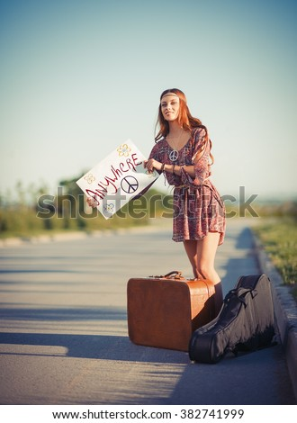 Portrait of a beautiful young hippie woman hitchhiking on the road - stock photo