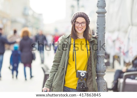 Portrait of a beautiful young hipster girl with an old-fashion camera looking at camera and smiling - stock photo