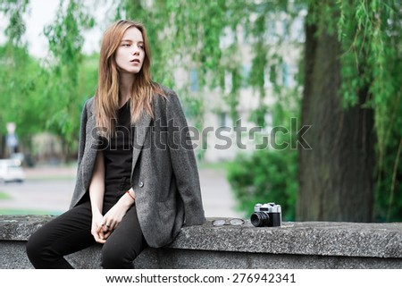 portrait of a beautiful young hipster girl with the camera in the city in the spring - stock photo