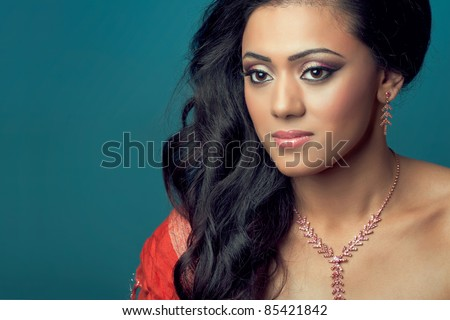 Portrait of a beautiful young indian/asian model with long hair, isolated on blue - stock photo