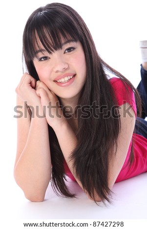 Portrait of a beautiful young Japanese teenager high school student girl lying on the floor, with long black hair wearing blue denim jeans and a pink t shirt with big happy smile. - stock photo