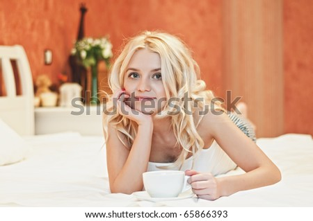 Portrait of a beautiful young lady drinking her morning coffee in couch - stock photo