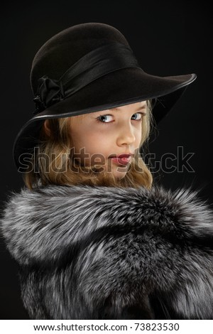 Portrait of a beautiful young lady in gray fur coat and black hat looking through a shoulder on a dark background