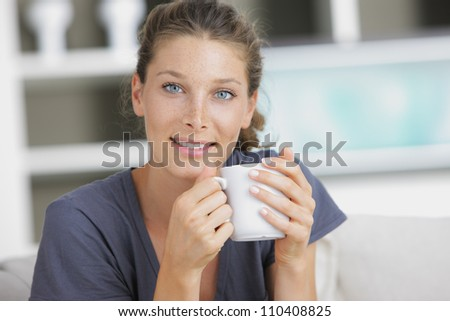 Portrait of a beautiful young lady with cup - stock photo