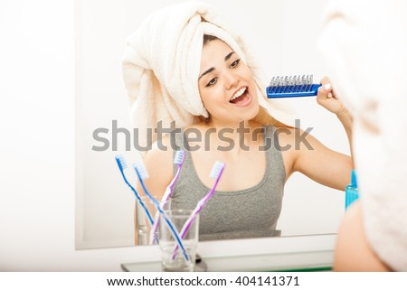 Portrait of a beautiful young Latin woman having fun in the bathroom and singing to a hairbrush - stock photo