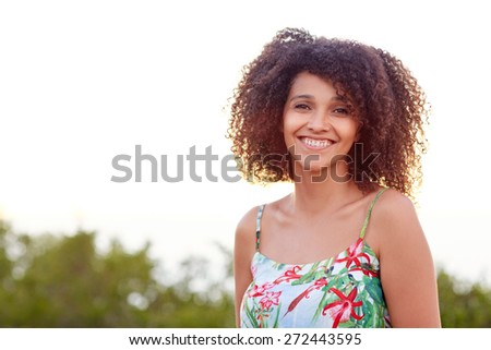 Portrait of a beautiful young mixed race woman smiling outdoors in a park - stock photo