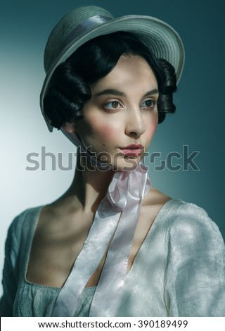 Portrait of a beautiful young model in a vintage attire. Hat and dress. Cinema style color.