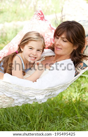 Portrait of a beautiful young mother and daughter laying and relaxing together on a hammock during a sunny summer day on holiday home garden. Family relaxing outdoors, healthy and wellness lifestyle. - stock photo