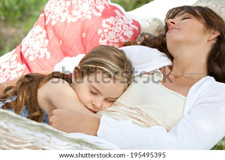 Portrait of a beautiful young mother and daughter laying down relaxing and sleeping together on a hammock during a sunny day in a holiday home garden. Family relaxing outdoors, healthy lifestyle. - stock photo