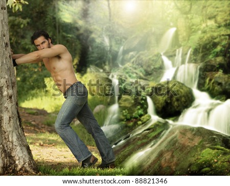 Portrait of a beautiful young muscular man leaning against a tree in a beautiful, heavenly place - stock photo