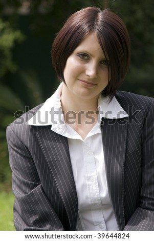 Portrait of a beautiful young professional woman with a black pinstripe suit. - stock photo