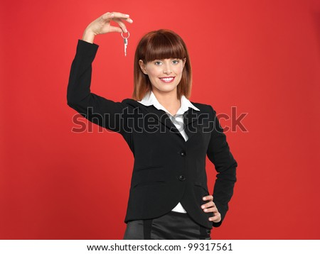 portrait of a beautiful, young realtor businesswoman, holding a house key in her hand, on red background - stock photo