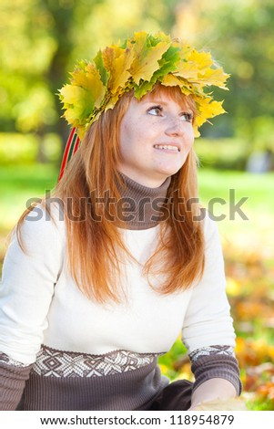 portrait of a beautiful young redhead teenager woman in a wreath of maple leaves - stock photo