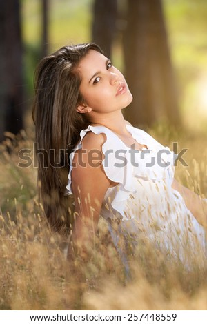 Portrait of a beautiful young serene woman sitting in a meadow - stock photo