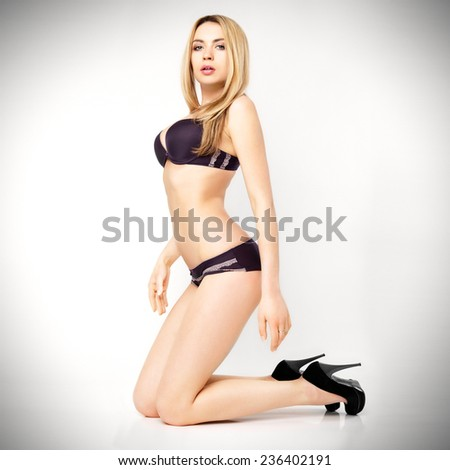 Portrait of a beautiful young sexy woman on gray background.  - stock photo