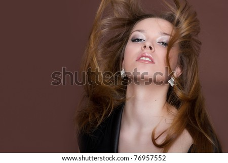 Portrait of a beautiful young sexy woman with long flying hair, studio shot