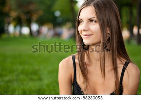 Portrait of a beautiful young smiling woman in green summer city park