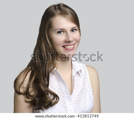 Portrait of a beautiful young smiling woman isolated on a gray background