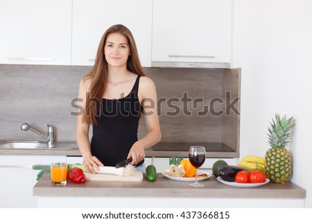 Portrait of a beautiful young smiling woman. Young girl cooking in the new kitchen. Preparing vegetable salad.