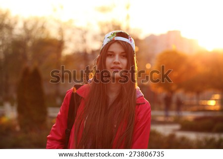 Portrait of a beautiful young traveler woman with a backpack, bright orange sunset light, traveling along Europe, freedom and active lifestyle concept - stock photo