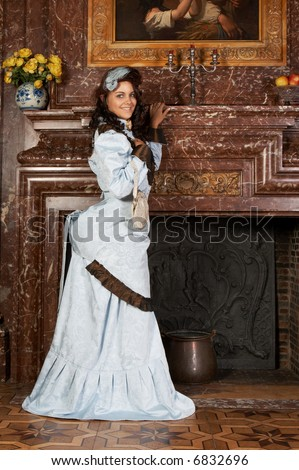 """Portrait of a beautiful young victorian lady in a genuine bustle dress. Shot in the antique castle """"Den Brandt"""" in Antwerp, Belgium (with signed property release for the Castle interiors). - stock photo"""