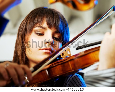 portrait of a beautiful young violinist playing indoors - stock photo