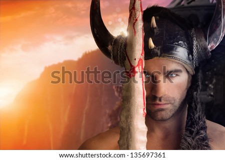 Portrait of a beautiful young warrior holding sword with fantasy background - stock photo