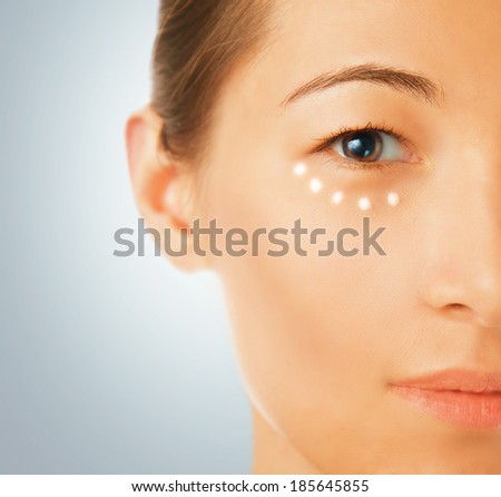 Portrait of a beautiful young woman, a cream applied around the eye, concept of skincare - stock photo