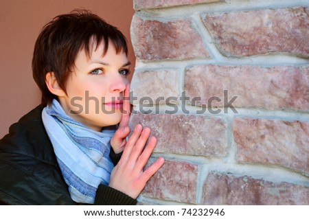 Portrait of a beautiful young woman against a wall.