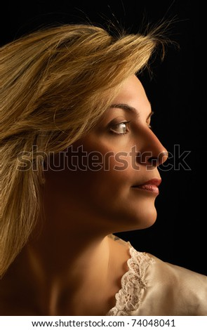 Portrait of a beautiful young woman against dark background, looking sideways - stock photo