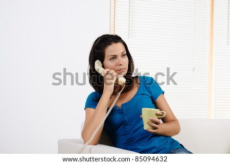 Portrait  of a beautiful young woman, angry and talking on the phone. - stock photo